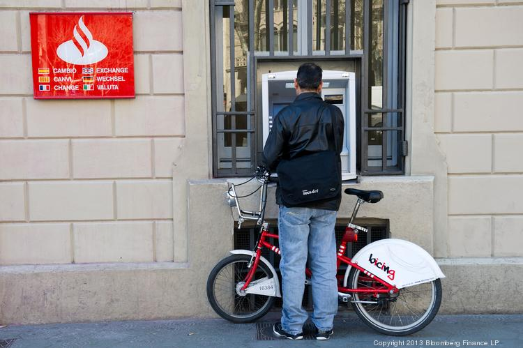 A customer uses a Banco Santander ATM in Barcelona, Spain, in March 2013. The bank's Sovereign subsidiary –set to change its name to Santander in October – is bringing ATM-enabled smart cards to the U.S. for the first time, at two Massachusetts college campuses.