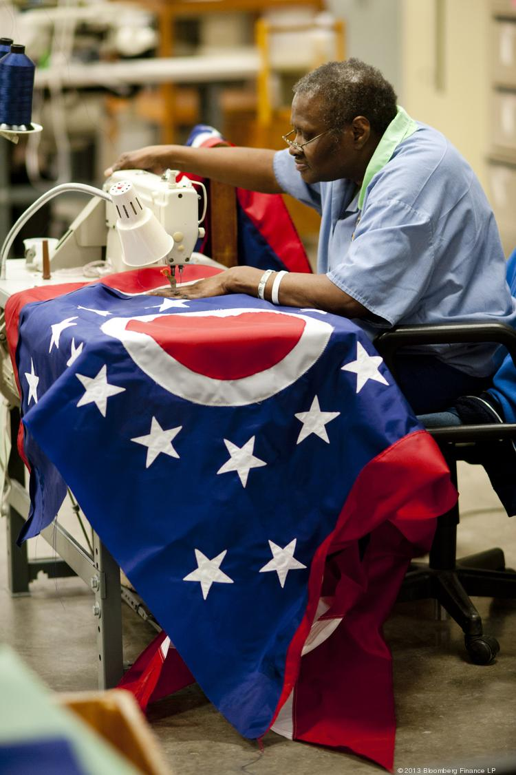 An inmate sews an Ohio state flag in the Prison Industries building at the Ohio Reformatory for Women in Marysville, Ohio, on Wednesday. Manufacturers boosted production in February heading into U.S. budget cuts and political squabbles this month that hurt consumer sentiment, reports showed.