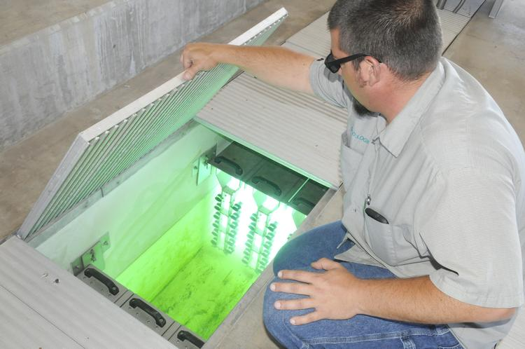 Justin Gregory keeps the shades on while checking out the ultraviolet light bulbs that are used to disinfect the water.