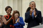 President Barack Obama and first lady Michelle Obama applaud from the steps of the Lincoln Memorial.