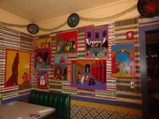 Brightly-colored decorative art lines the walls of this dining room.