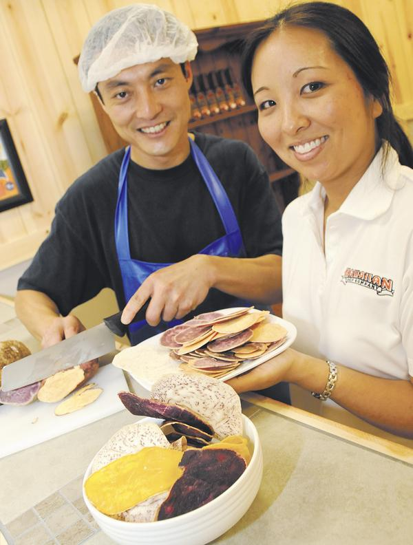 Hawaiian Chip Co. owner James Chan and his wife, Kammy, the company's retail store manager, cut fresh sweet potato and taro for a made-to-order bag of chips in their new store in Kalihi.