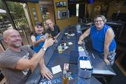 "Kobalt bar patrons, from left, Jesse Lujan, Doug Pesavents and ""Olive"" toast one another at the Park Central Mall location as bartender Scotty Jones looks on."