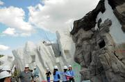 SeaWorld guides and members of the media walk amid the towering recreation of rock and glacier formations.