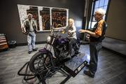 Christine Fleissner of Assurant Health gets a lesson on how to ride a Harley by Harley-Davidson employee Gary Schoneman, while her husband Dick watches.