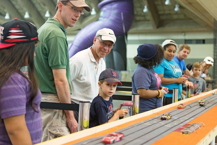 Jeff Hoffheins, center, and his son-in-law, Michael Kersten, watch as Charles Kersten, 6, races the slot cars at the Family Fun Zone in the Baltimore Convention Center on day 1 of the 2013 Grand Prix of Baltimore.