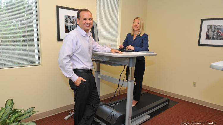 If you get a job at Laurel-based Aquilent, you can use this treadmill work station. Pictured here are CEO David Fout and Nancy Bilotto, vice president of human resources.