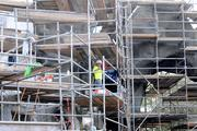 Workers navigate scaffolding as they add the finishing touches to a section of scenery.