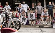 """People who lined the street held """"Welcome Home"""" signs for the riders."""