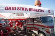 Parking lots were full of tailgaters well before game time. Tom Thiry, in the No. 37 jersey, and his wife, Debbie, right, bought their OSU-themed van three years ago from a veteran tailgater who only drove it to games. The 1986 model van had only 32,000 miles on it. On Saturday, they were tailgating with Ed Kagels, seated, Allen White, in the No. 10 jersey, and George Gans behind White.