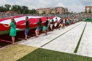A giant U.S. flag was stretched across the field for opening ceremonies. The 49ers beat the Campbell Fighting Camels 52-7 in their inaugural football game at Jerry Richardson Stadium, on Aug. 31, 2013.