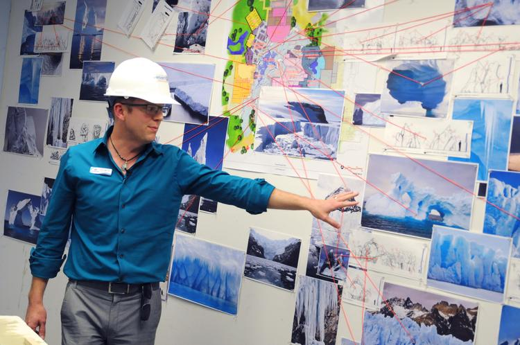 Brian Morrow, senior director of attraction development and design, points out reference photos of ice formations used in the development of Sea World's Antarctica.
