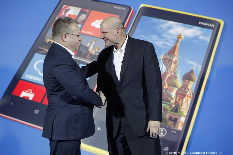 Steve Ballmer, chief executive officer of Microsoft Corp., right, and Stephen Elop, chief executive officer of Nokia Oyj, shake hands after a presentation of the new Nokia Lumia 920 smartphone at a news conference in 2012 in Moscow. Elop will receive a compensation package worth about $25.5 million when he rejoins Microsoft as an executive.