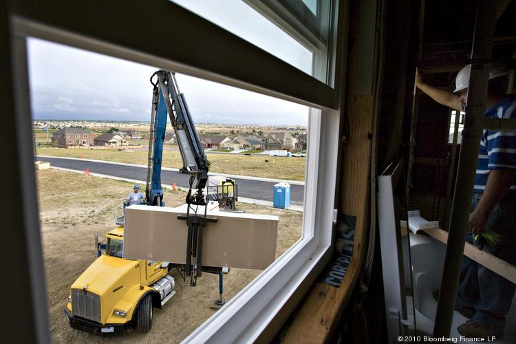 Workers unload drywall for a house under construction in Thornton.