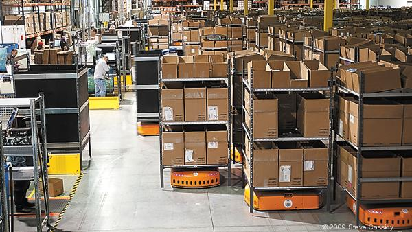 Orange robots bring shelving with boxes to Amazon workers on the floor.