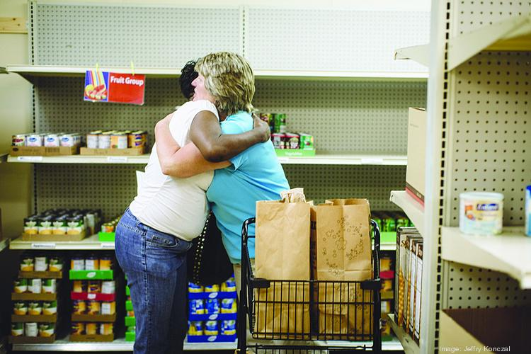 Healthy Worthington Resource Center and Food Pantry volunteer Jennie Arnold, right, comforts a client.