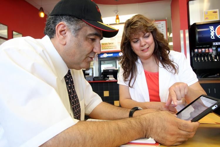 Pizza 9 CEO Hass Aslami, left, works with franchisee Julie Johnson at the local chain's location on Albuquerque's Westside, 6541 Paradise Blvd. NW.
