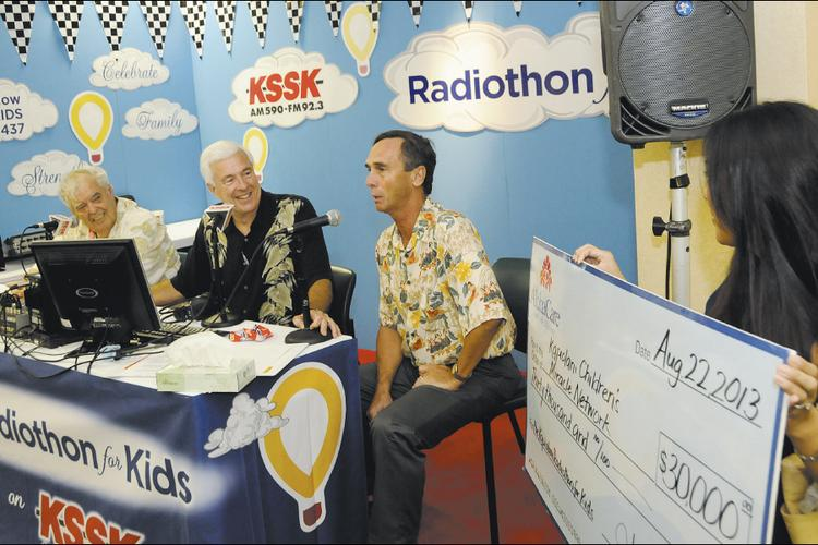 Senior Director of Community Relations for Aloha Care Daryl Huff, second from right, goes on the air with KSSK radio personalities Larry Price, far left, and Michael W. Perry during the Kapiolani Radiothon for Kids. Aloha Care Marketing Specialist Rachel Mark, far right, holds a check representing Aloha Care's $30,000 donation to the Kapiolani Children's Miracle Network. —  Tina Yuen, PBN