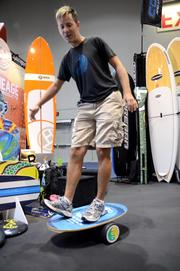 Jonathan Meacham, owner of Epic Boardsports in Cocoa Beach, practices his balance before checking out the exhibit area.