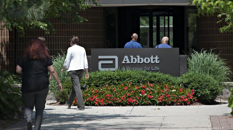 Employees Walk Near An Abbott Laboratories Sign At The Companys Headquarters Complex In Park