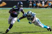 Seattle Seahawks fullback Derrick Coleman tries to dodge a lunging tackle by Panthers linebacker Thomas Davis.