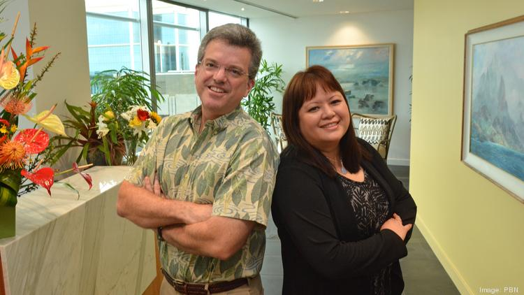 Chun Kerr Law Firm partners Andrew Bunn and Janel Yoshimoto pose for a photo in their new office on the 21st floor of the First Hawaiian Center.