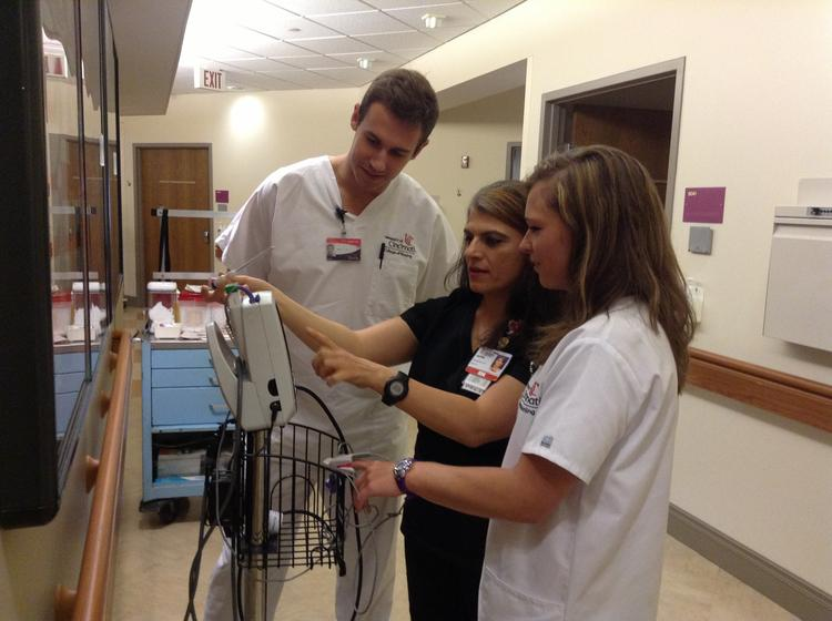 Fatin Mangold (center), a registered nurse at the University of Cincinnati Medical Center, instructs UC College of Nursing juniors Kevin Milligan and Heather Brunswick.