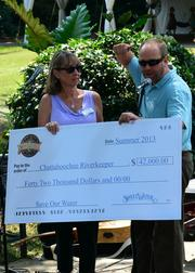 Sally Bethea, founding director and Riverkeeper for the Chattahoochee Riverkeeper, gets a check from SweetWater.