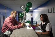 A passenger on the first flight, Brian Canady, left, checks in with Kara Kuhnhein, a customer service representative.
