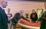 Maryland Live! Casino Vice President of Table Games Neal Sloane, center, speaks with President Robert Norton, left, as the first blackjack tables are delivered to the casino on Wednesday morning.