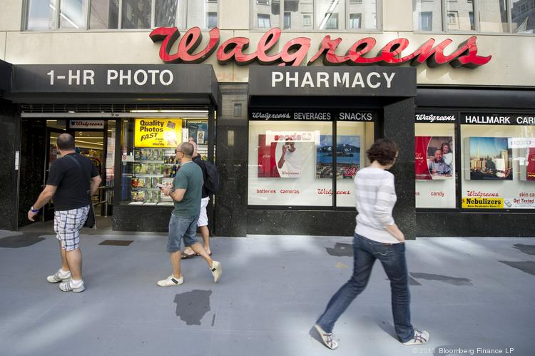 Pedestrians pass in front of a Walgreen Co. store.