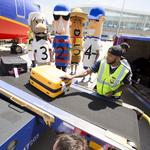 Brewers players try their hands at loading luggage, directing planes: Slideshow