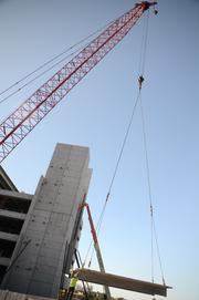A beam is lifted up to the top of the parking garage by a 180-foot crane.