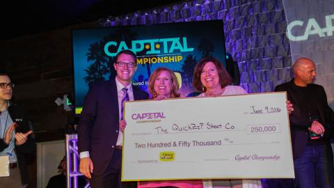David Brey of Capital Championship awards the QuickZip Sheet Company owners and founder, Caroline Portis and Elizabeth Sopher, with the $250,000 grand prize as winners of the 2016 Capital Championship Entrepreneurial Tournament.