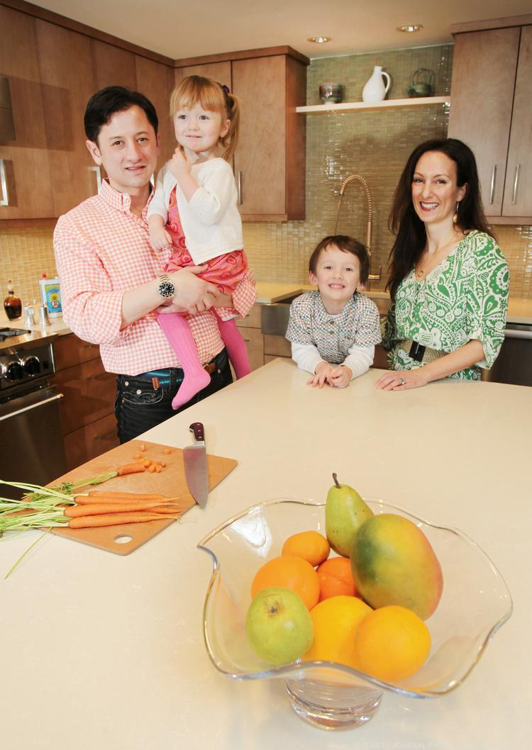 """Amy Bohutinsky, Zillow chief marketing officer, and her chef-architect husband, Francesco Crocenzi, in the kitchen of their newly remodeled home with their children, Frankie, 5, and Emilia, 2. """"Designing this kitchen was about two things: keeping the water as the main focal point of the room, and making this a functional place where people could also gather,"""" said Crocenzi."""