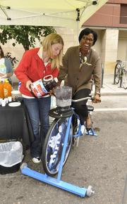 Jandel Allen-Davis tries her hand at the blender bike at LiveWell Colorado's event near 16th and Glenarm streets. She gets help from Taylor Roddy of Kaiser Permanente Colorado.