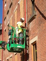Years of leaking downspouts resulted in water damage to nearby masonry. Workers repair the damage.