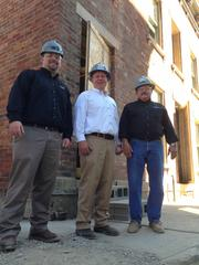 (From left) Bill Smith, senior project manager, Michael Breetz, partner, and George Fryman, superintendent, all with HGC Construction in front of a historic building in Mercer Commons Phase II. The entire front wall of the building behind them had to be rebuilt using the original bricks.