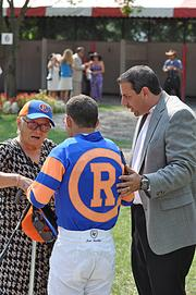 In the paddock before an Aug. 31 race at Saratoga, Repole and his grandmother (in hat) congratulate jockey Javier Castellano on the recent birth of his child. Castellano is riding Repole's horse, Hobbs.