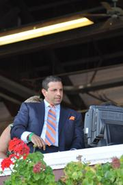 Another day, another race: Repole checks the TV screen to keep track of his horse, Caixa Eletronica, as the horses near the far turn of Saratoga Race Course.