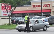A Colonie police officer directs traffic outside the store. Trader Joe's hired two to three officers to guide traffic and ensure the safety of pedestrians for the next 10 days. Police said traffic was moving smoothly, with no accidents this morning.