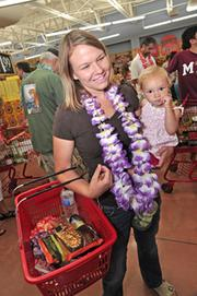 "Kristen Jensen, 29, of Albany, holds her 19-month-old daughter, Harper, as she stands in line at the new Trader Joe's in Colonie, New York. Jensen moved here from the Boston area four months ago. She said she used to drive weekly to the Trader Joe's in Hadley, Massachusetts, or to  Boston while visiting friends, to stock up. Her favorite item? Cookie Butter. ""It tastes like Christmas in a jar,"" she said."