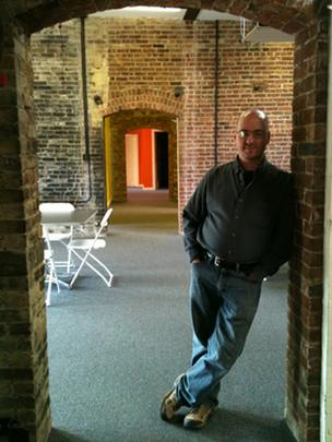 Enable Labs President Mark Menard stands in the doorway leading to the room where future training of software developers will take place. Enable Labs moved to new space on River Street in Troy to play a larger role in software development in the Capital Region.