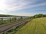 A cyclist makes it to the top of a hill overlooking the Mohawk River on the Mohawk-Hudson path on Bike to Work Day.