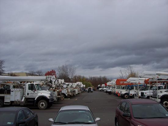 Utility trucks wait outside the Desmond Hotel and Conference Center in anticipation of power outages caused by Hurricane Sandy. As many as 8,000 people in the region lost power because of the storm.