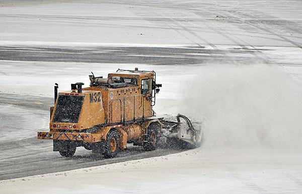 A plow clears a runway at Albany International Airport Friday.