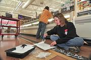 Rachel Galka, a Trader Joe's crew member, stencils race horses on a board that will decorate the new store in Colonie, New York. The store features other art work created by store employees, including brightly-colored murals depicting familiar scenes in the Capital Region.