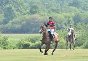 A player on the State Farm/The Villages polo team, based in Florida, charges up the field during a match at Whitney 2, the secondary field at Saratoga Polo Association.