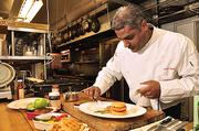 AJ Jayapal, food and beverage manager of the Rotterdam-based Mallozzi Group, preparing Miss Sydney's Marinated Lucki 7 Pork Chop with Savory Apple Bacon Waffles, roasted parsnips & Indu's Chutney Jus,at Colonie Country Club in Voorheesville.