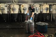 Lee McCrea cleaning kegs at Brown's Brewing Co. in Troy.